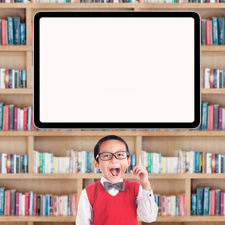 Joyful male primary school student pointing at a blank whiteboard in the library