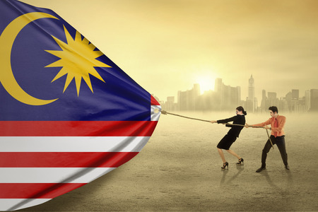 Portrait of two young asian people pulling a flag of malaysian, shot outdoors