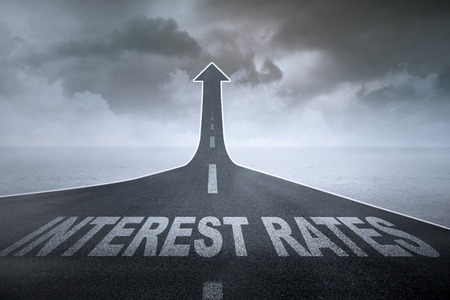 Higher interest rates concept: The words interest rates on a straight road turning into ascending arrow