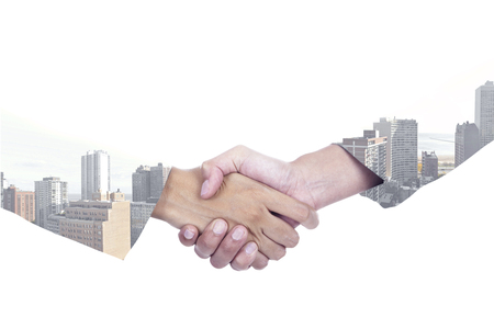 Double exposure of two entrepreneurs shaking hands with a city background, isolated on white
