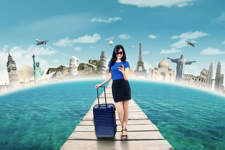 Photo pour Beautiful female tourist standing on the jetty while carrying bag and sending message with mobile phone - image libre de droit