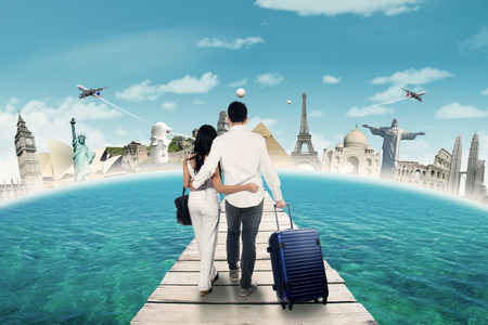 Rear view of two tourists walking on the bridge and going to honeymoon at the world monuments