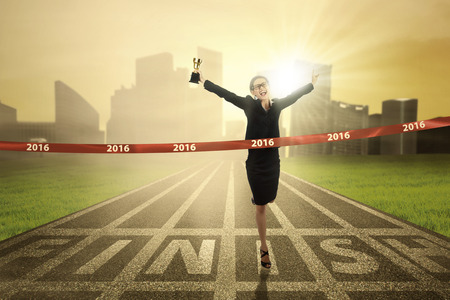 Photo pour Photo of young business woman winning the race competition and crossing the finish line while carrying a trophy - image libre de droit