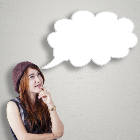 Photo of beautiful teenage girl thinking idea while looking at blank bubble speech