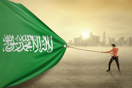 Image of young businessman pulling a flag of Saudi Arabia, shot outdoors