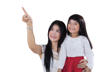 Portrait of young asian mother with her daughter looking and pointing at copy space in the studio