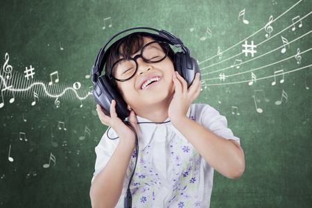 Female primary school student wearing glasses and smiling while listening music in the classroom