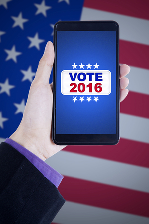 Image of hand holding mobile phone with vote button on the screen, shot with american flag background
