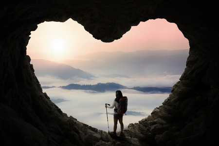 Foto de Silhouette of female hiker standing inside cave shaped heart symbol while holding stick pole and enjoy mountain view - Imagen libre de derechos