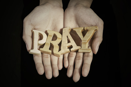 Close up of prayer hands showing a word of pray in dark background