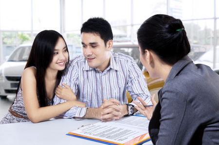Picture of two young car buyers discussing with a female car dealer in the showroom
