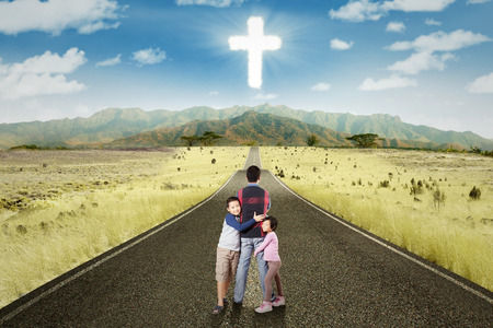 Two cute children hugging their father on the road with a cross sign on the sky