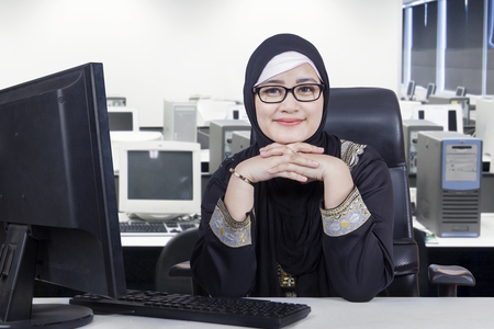 Photo pour Photo of Arabic young businesswoman sitting in the office room while smiling at the camera and wearing veil with computer on desk - image libre de droit
