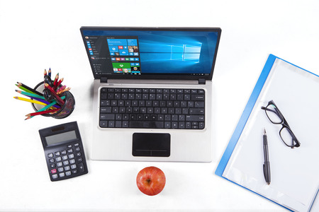 JAKARTA, SEPTEMBER 02, 2015: Closup of stationery and laptop computer using the new software of windows 10