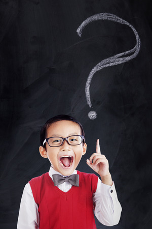 Picture of a cheerful primary school student wearing uniform in the class with question mark on the blackboard