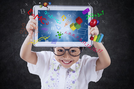 Photo for Cute little girl smiling at the camera while holding a digital tablet with formula of science, math, and physics on the screen - Royalty Free Image
