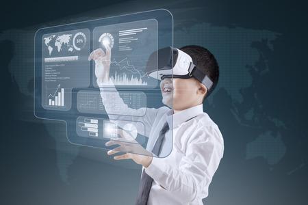 Photo pour Little boy wearing virtual reality headset while touching financial graph on the virtual screen - image libre de droit