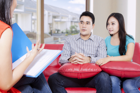 Photo for Husband and wife are consulting of their problem by psychiatrist while sitting on the red couch in the house - Royalty Free Image