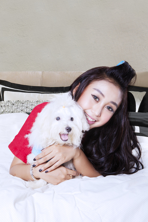 Portrait of young woman smiling and looking at the camera while embracing her puppy in the bedroom