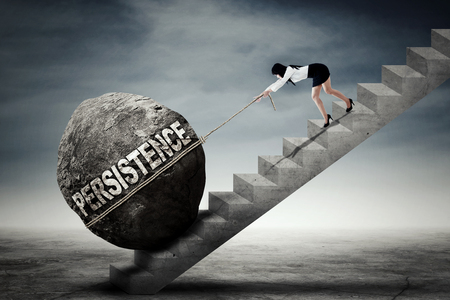 Foto de Young Asian businesswoman pulling a big stone with persistence text while climbing up a ladder - Imagen libre de derechos