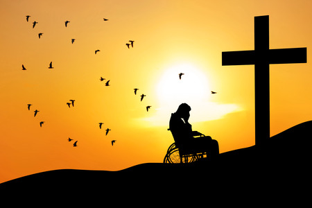 Silhouette of disabled male sitting on a wheelchair and praying for hope by the cross in the sunset