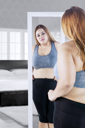 Photo pour Image of overweight young woman looking at the mirror while touching her belly in the bedroom - image libre de droit