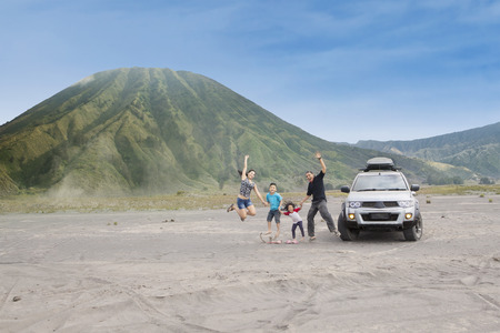 Joyful family jump on volcanic desert, shot outdoors