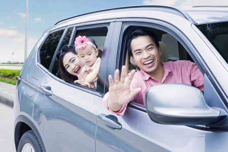 Portrait of happy family looking out car window while smiling at the camera in the highway