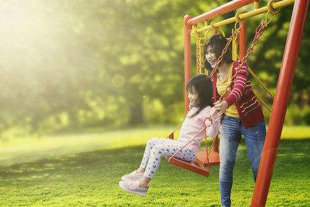 Photo pour Portrait of little daughter and mother playing swing in the park while smiling together - image libre de droit