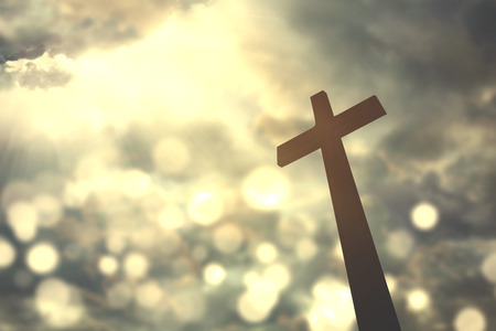 Silhouette of christian cross symbol with bright sunlight on the sky