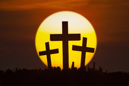 Silhouette of three crucifixes above the city with a golden sun, shot at sunset time