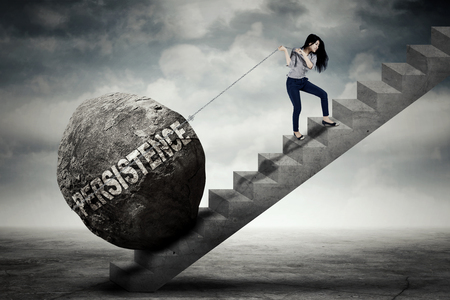 Young female entrepreneur is pulling big stone with persistence word while climbing on the stair
