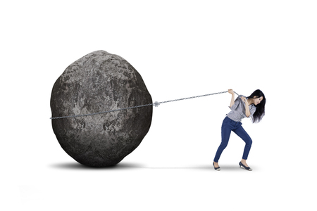 Photo for Young female entrepreneur is pulling big stone with a chain, isolated on white background - Royalty Free Image
