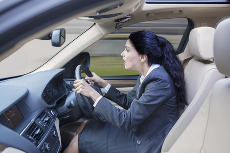 Picture of Indian businesswoman driving a car fast while wearing formal suit and looking at the road