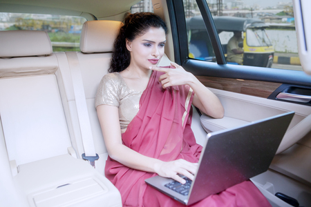 Picture of a female Indian entrepreneur working with a laptop computer while sitting in a car on the road