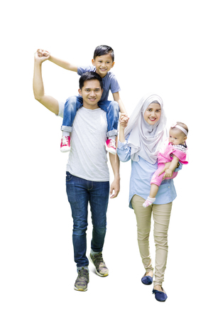 Photo pour Full length of muslim family walking in the studio while the father carrying his son on shoulder - image libre de droit