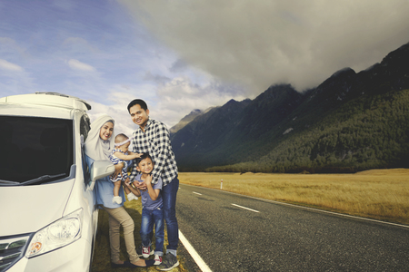 Image of Muslim family resting and standing near their car while travelling in the mountain