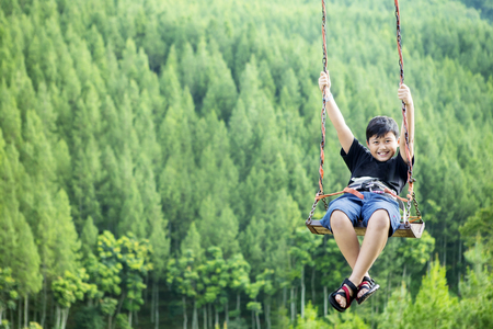 Photo pour Image of little boy looks happy while playing on a swing with a beautiful pine forest - image libre de droit