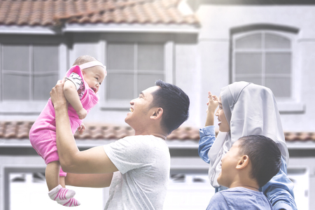 Photo pour Two muslim parents playing with their baby and son at new house outside - image libre de droit