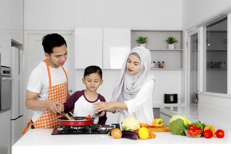 Foto de Photo of Muslim family cooking together while preparing food in the kitchen - Imagen libre de derechos