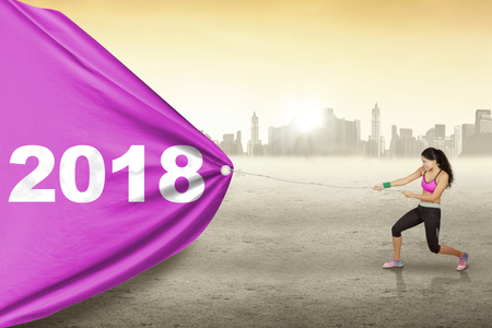 Photo pour Young woman wearing sportswear while pulling numbers 2018 in a banner with city background - image libre de droit