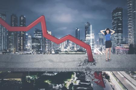 Asian businesswoman having headache while standing near downward arrow on the bridge