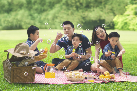 Photo pour Picture of Asian family is blowing bubble soap while enjoying their holiday and picnicking in the park - image libre de droit