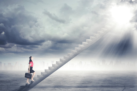 Photo pour Businesswoman walking up staircase to door in sky with bright light shining down - image libre de droit