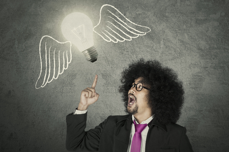 Afro businessman getting and idea represented with light bulb flying with wings