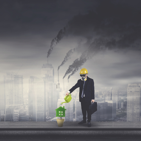 Young businessman wearing a gas mask while watering a plant in the pot. Shot with polluted city background