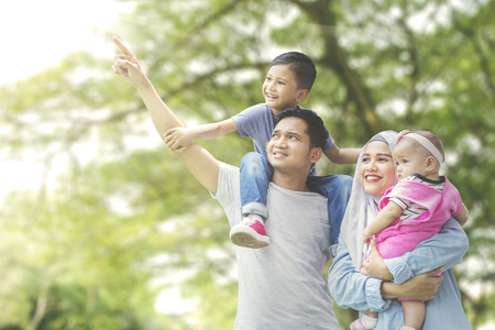 Foto de Picture of Muslim family looking at something while standing together in the park - Imagen libre de derechos