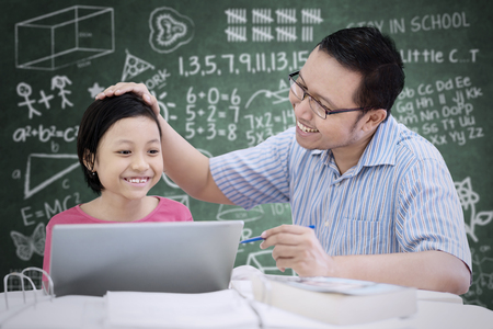 Photo pour Portrait of Asian cute schoolgirl being praised by her teacher while sitting in the classroom - image libre de droit
