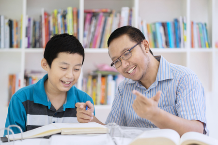 Photo pour Picture of male teacher guides his student to count while sitting in the library - image libre de droit