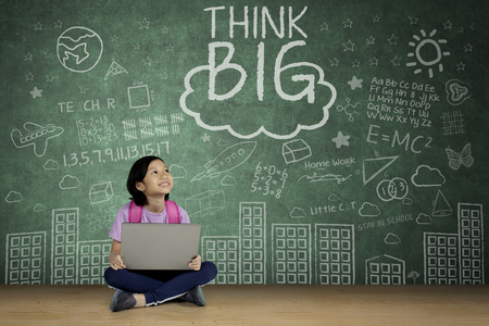 Portrait of a cute schoolgirl looking at word of think big on a chalkboard while studying with a laptop